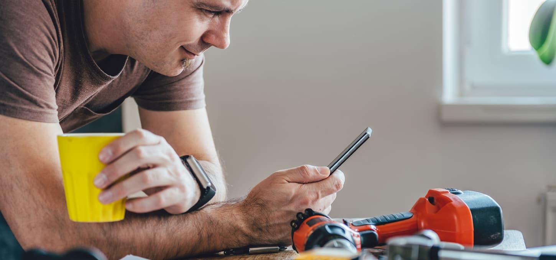 Håndverker som drikker kaffe og scroller på mobiltelefonen sin i pausen