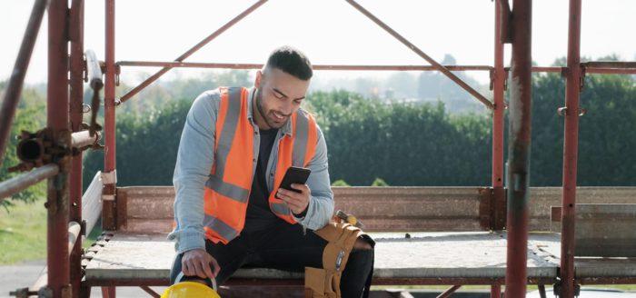 Håndverker sjekker mobilen ute på byggeplass