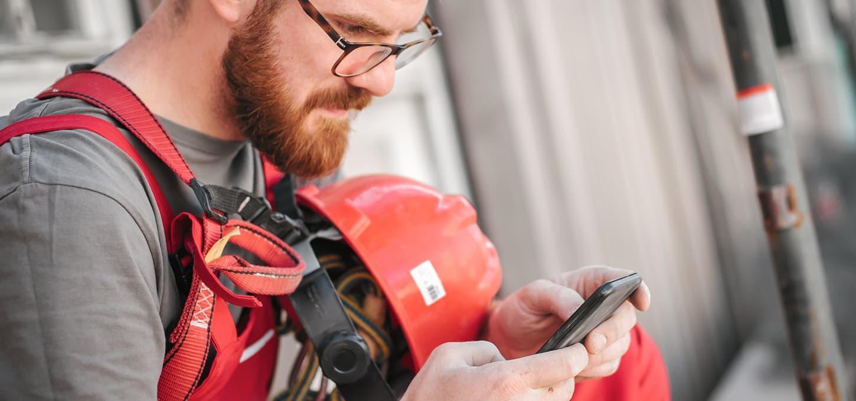 Arbeider sjekker mobilen på byggeplassen